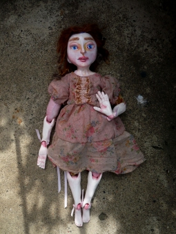 dreamy image of a sculpted art doll in vintage clothing