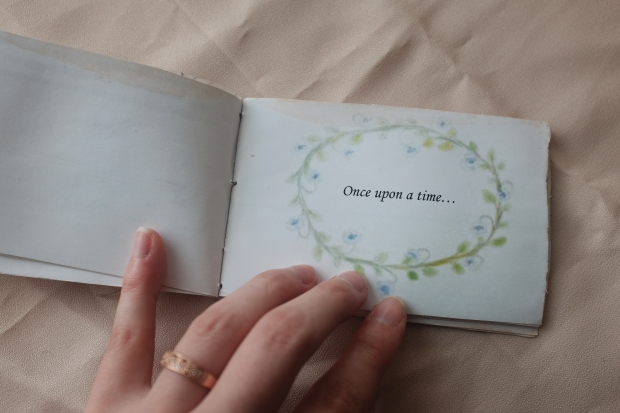 """once upon a time"" page in an illustrated miniature fairy tale book"