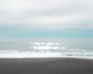 out of focus image of grey sand and sparkling blue ocean water