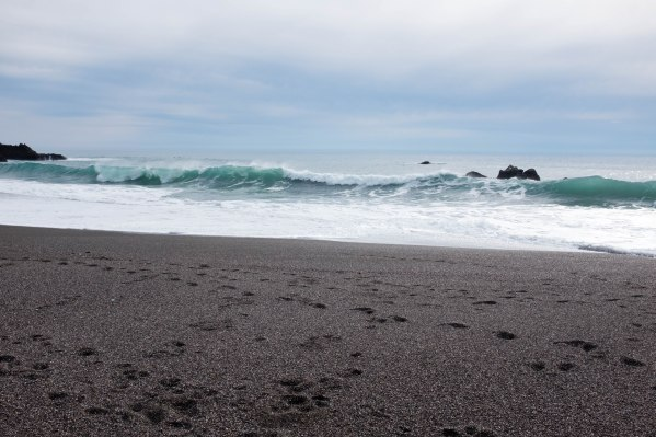 blue ocean wave with black rocks and black sand