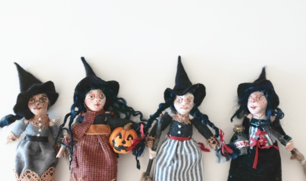 a group of four handmade miniature witches for halloween decorations