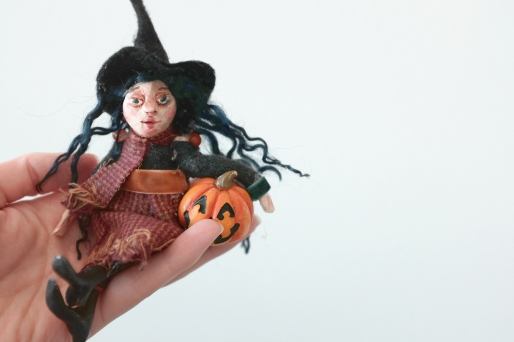 handmade miniature halloween pumpkin witch holding a jack o lantern