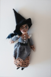 miniature halloween witch in an elegant dress and witch hat
