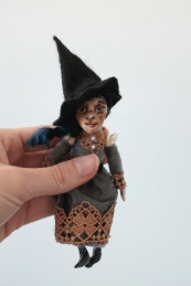 miniature elegant witch doll with a big black witch hat
