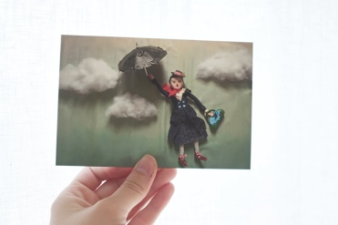 a hand holding up a postcard with an image of Mary Poppins flying through the sky with her umbrella