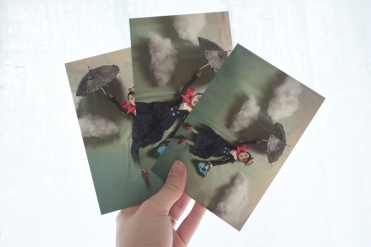 hand holding up three postcards featuring blue and red images of mary poppins