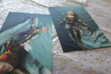 three peter pan postcards scattered over a desk covered in vintage pastels and sparkling stars