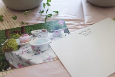 desk in soft vintage pastels showing postcards and letters