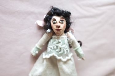 miniature art doll of a victorian girl in green and pink with black curly hair