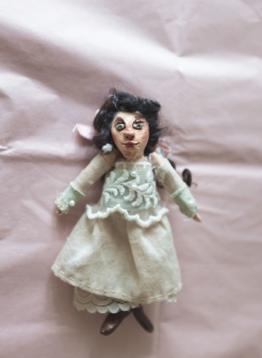 miniature art doll wearing a white and green victorian lace dress