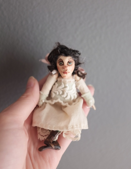 hand holding a miniature victorian doll