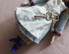 close up of a miniature doll holding a tiny ring of keys