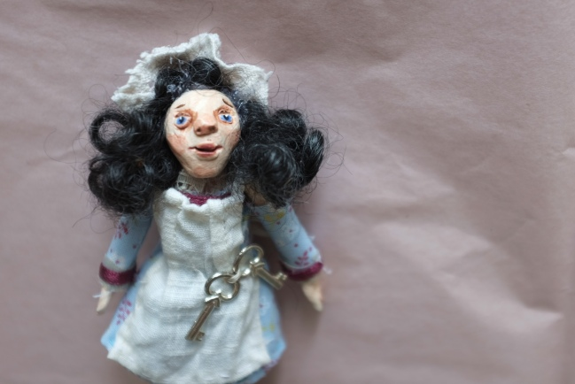 miniature art doll dressed as a maid, with lace cap and curly hair