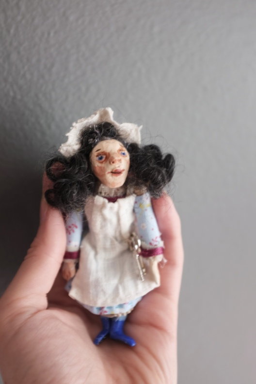 hand holding a miniature art doll in period clothing, to show scale