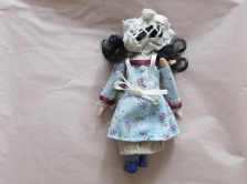 back of a miniature doll wearing period clothing, showing lace cap, apron, and tiny buttons