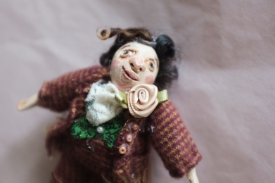 miniature art doll of a victorian gentleman with curly hair and a rose