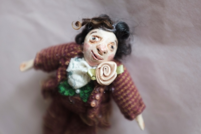 miniature doll of a victorian gentleman wearing a suit with a rose