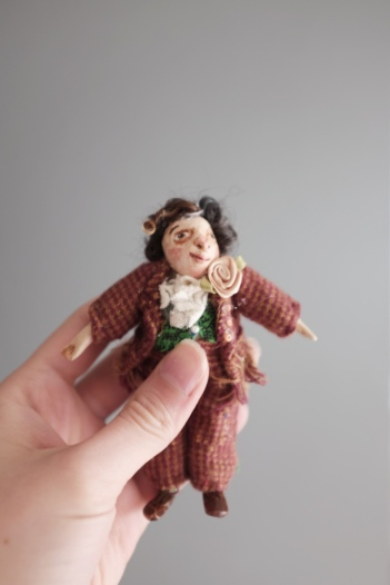 hand holding a miniature victorian man doll to show scale