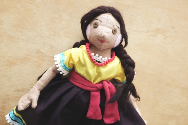 cloth doll of a girl from Mexico with braids and a colorful dress