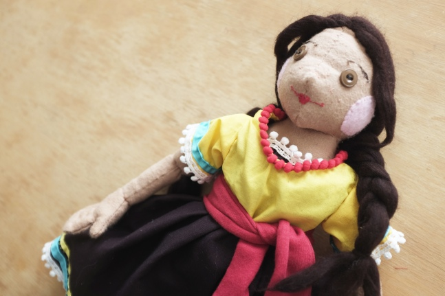 a handmade cloth children's doll of a mexican girl in a brightly colored dress