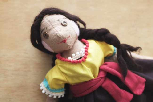 cloth children's doll with two braids wearing a Mexican dress