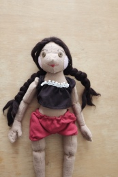 cloth doll of a hispanic girl with two braids