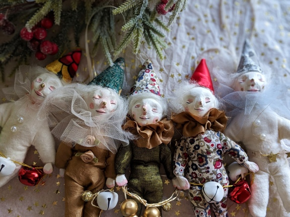 group of five sleeping elf christmas ornaments in elegant red, green, and gold