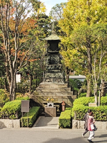 stone tower monument or shrine surrounded by fall foliage in tokyo