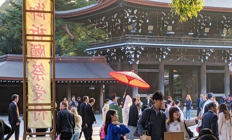 a shinto wedding party walks down the street through the meiji-jingu shrine in tokyo japan