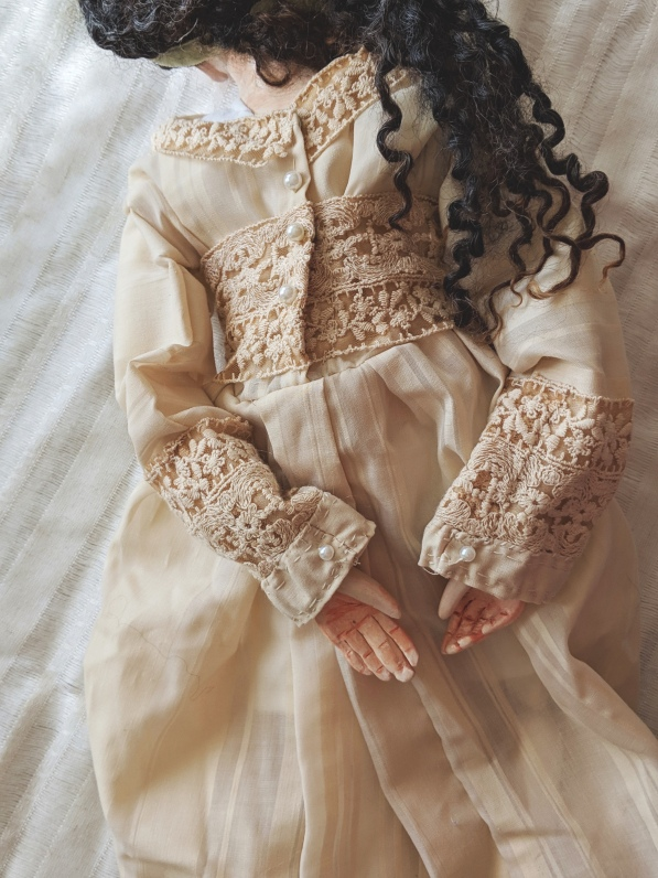 antique linen doll dress with delicate hand stitching, lace, and pearl buttons