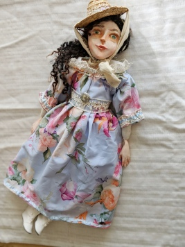 historic art doll in blue floral regency dress and straw hat