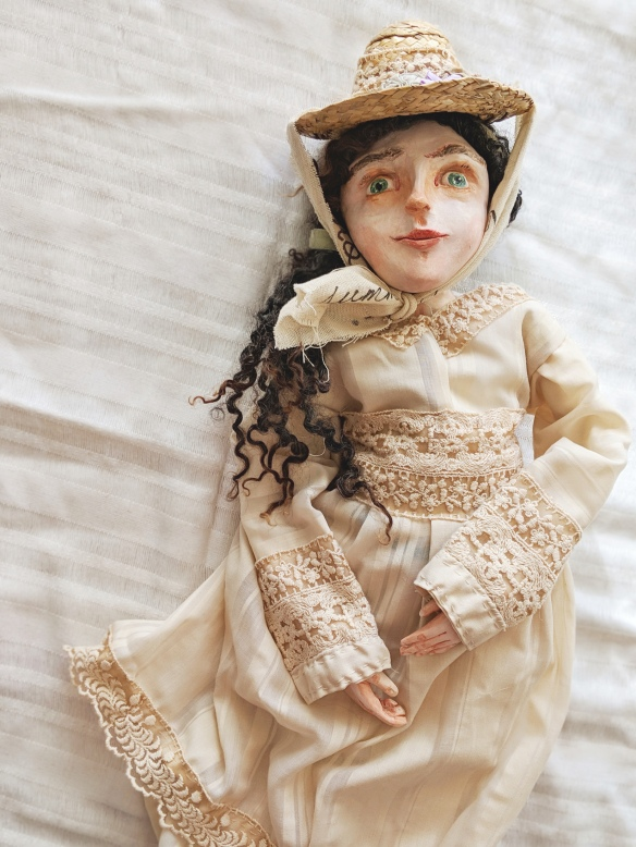 art doll sculpted from paperclay, with historic costume of linen and lace dress and straw hat